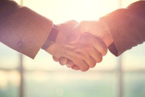 Zwei Männer besiegeln mit Handschlag die Gründung einer GmbH